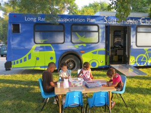 Kids drawing at the LRTP kids table outside the community conversations bus.